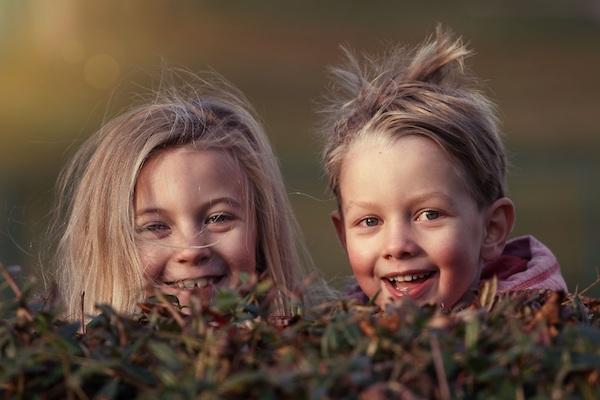 Zwei Kinder hinter einer Hecke