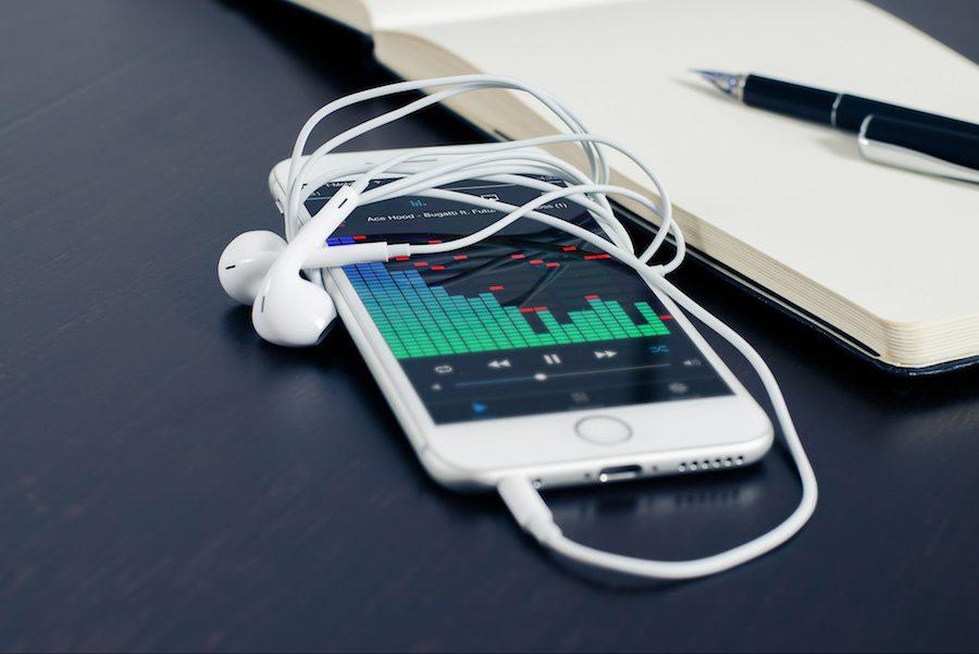iPhone mit weißen Kopfhörern auf einem Tisch