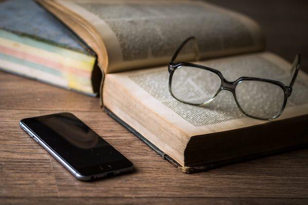 iPhone mit Buch auf dem eine Brille liegt